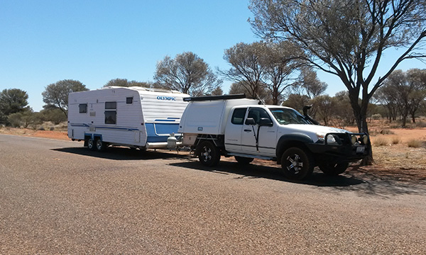 Ken and Margaret's 4WD vehicle and caravan parked under the shade of a roadside tree