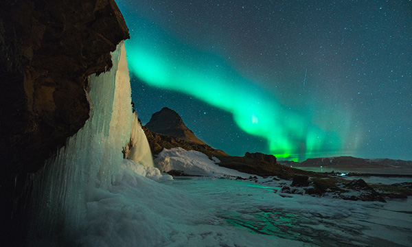 The beautiful hazy green lights of the Aurora Borealis in an icy landscape