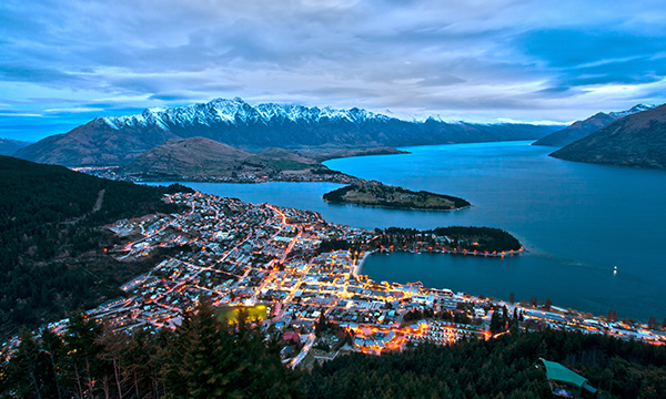 View of Queenstown city lights, looking towards the lake and surrounding snow-capped mountain peaks
