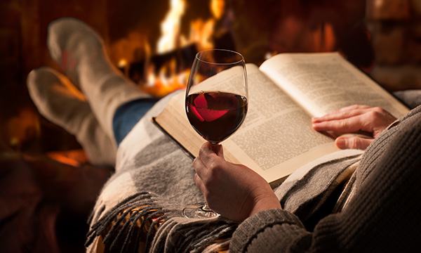 Reading a book in front of a fireplace with a glass of red wine